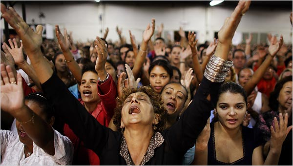A woman with an audience behind her hands up praising God